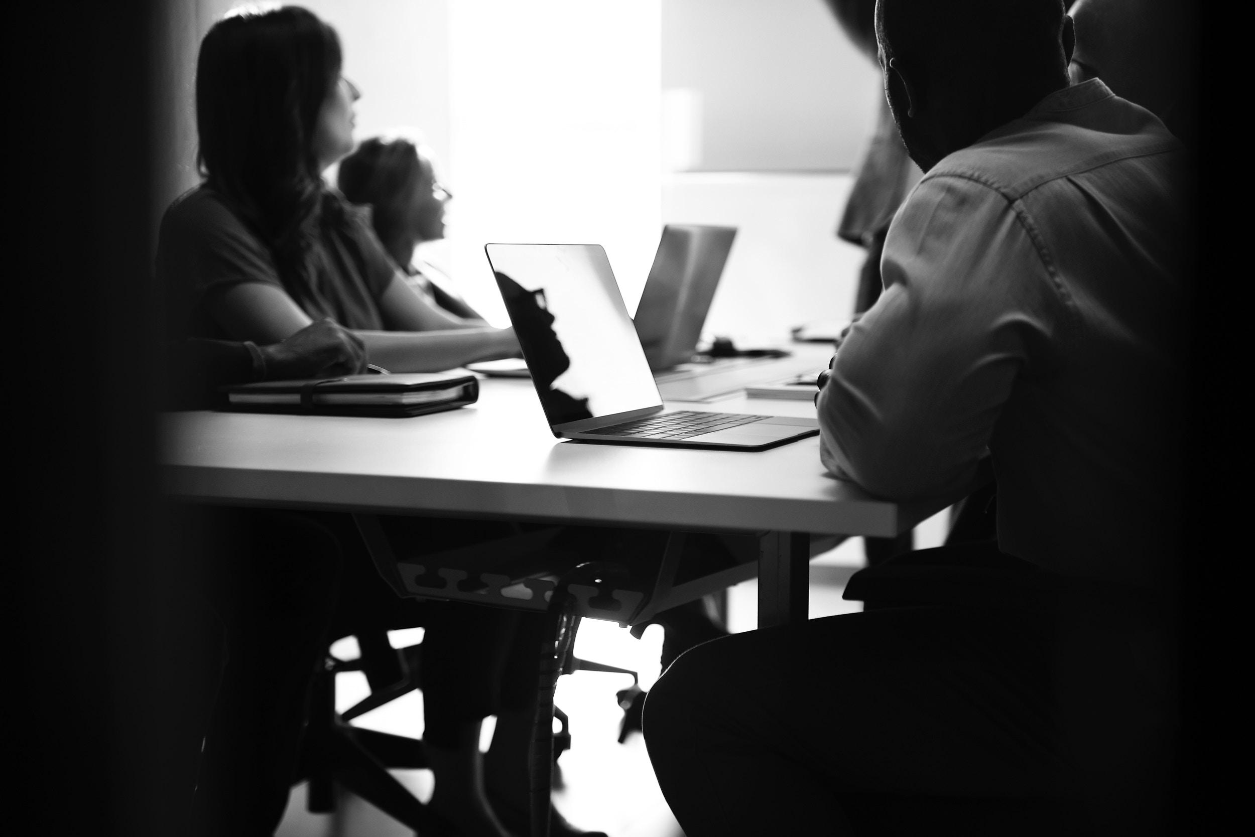 Menschen am Tisch mit Laptops vorsich schauen gemeinsam in eine Richtung.