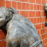 Zwei Bronze-Skulpuren zeigen Männer, die an einer Mauer lauschen