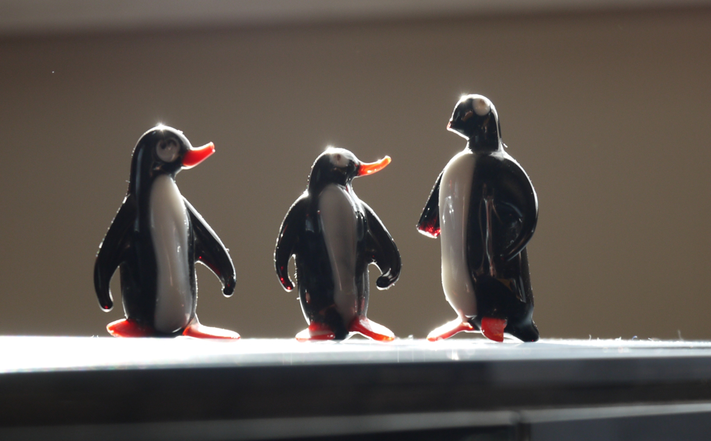 """Drei Pinguine aus Glasbläserarbeit stehen nebeneinander und """"schauen"""" auf den Größten mit abgebrochendem Schnabel"""