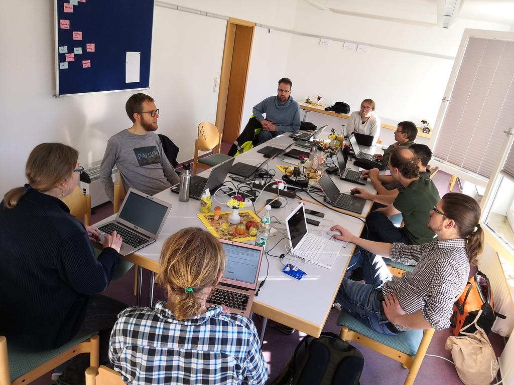 Arbeitsgruppe um einen Tisch, Laptops, Kabel.