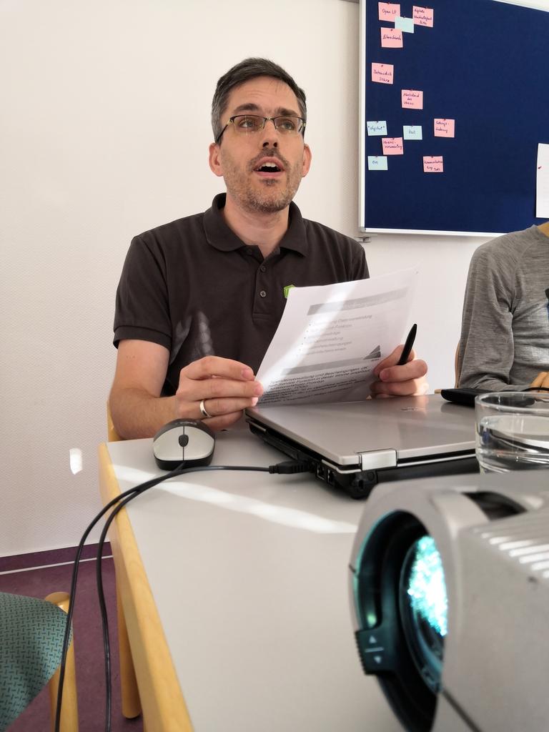 Timotheus präsentiert OpenPetra: Er sitzt an einem geschlossenen Laptop, hält Zettel in der Hand und spricht. Im Vordergrund ein Ausschnitt aus der Front eines Beamers.