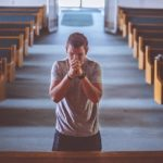 Ein Mann steht alleine vor dem Mittelgang einer Kirche Richtugn Altar in Gebetshaltung