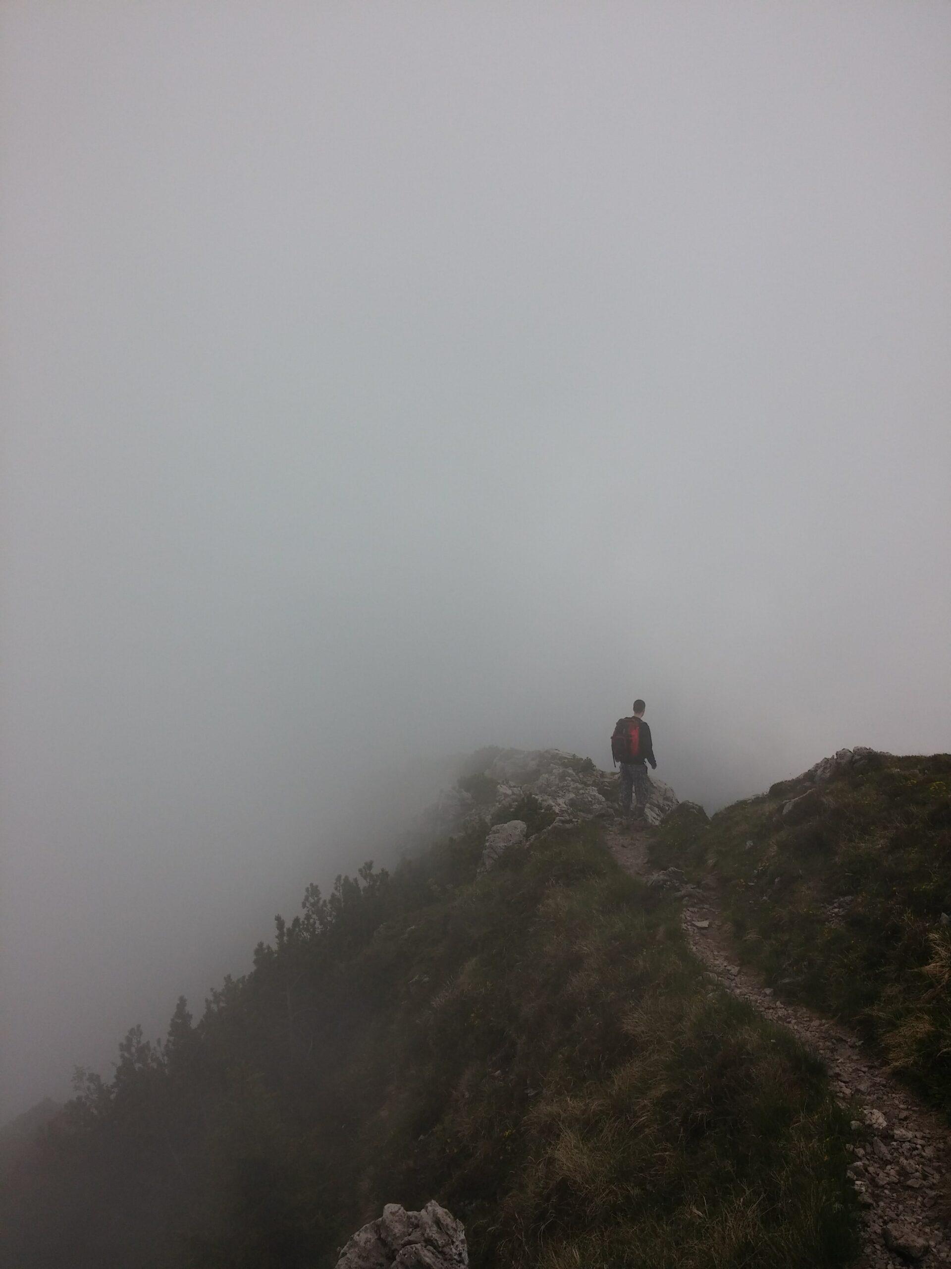 Ein Mann auf einem Berg vor einer Nebelwand