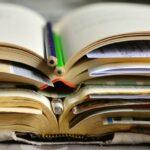 Ein Stapel aufgeschlagener Bücher mit Stiften dazwischen