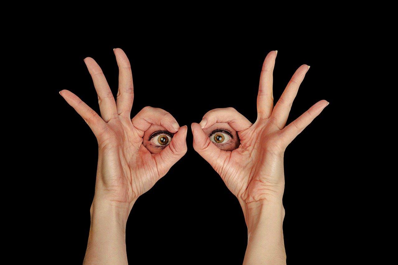 Eine Frau hält sich ihre Hände wie mit einer Brille vor die Augen. Der Rest des Gesichtes ist ausgeschnitten und geschwärzt.